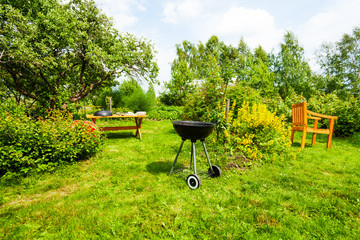 Beautiful view on garden with grill, table, chair