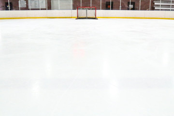 Perspective of a tiny hockey net across expansive ice at an indoor rink