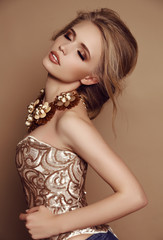 woman with blond hair in elegant golden dress and luxurious necklace