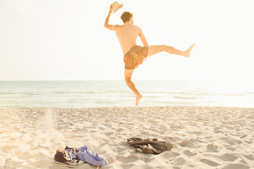 Freedom! A young man getting rid of clothes on a hot summer day, jumping up in swimwear running to the sea to jump into the water and swim