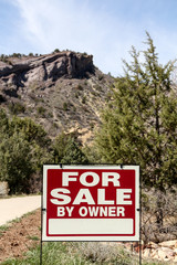 Blank for sale sign on land with a rocky cliff behind