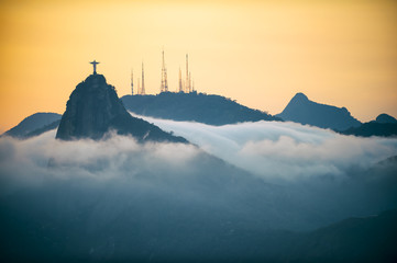 Corcovado mountain Christ the Redeemer standing in golden sunset above swirling mist clouds Rio de Janeiro Brazil
