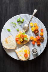 Bruschetta with a Mix of Red, Orange and Yellow Cherry Tomatoes and Basil Leaves
