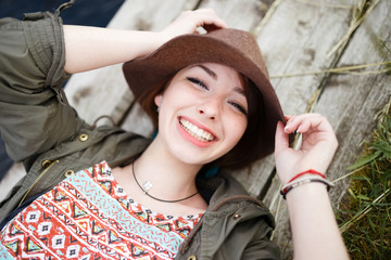 Bright stylish lifestyle portrait of pretty girl posing at hat.