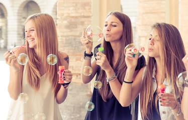 three young woman making soap bubbles