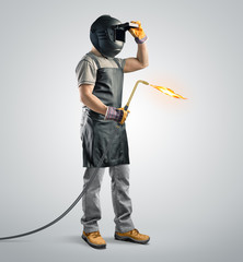 worker welder in a protective mask with gas welding machine