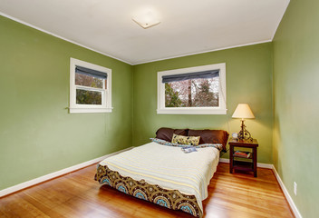 Boho themed bedroom with green walls, and hardwood floor.
