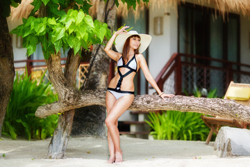 Young beautiful girl on the beach of a tropical island. Summer