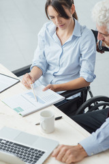 Woman on wheelchair working at desk