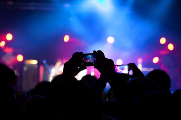 People at rock concert taking photos with cell phone