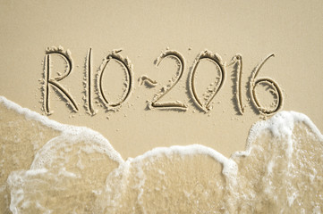 Simple Rio 2016 message handwritten in clean numbers on smooth sand beach in Rio de Janeiro Brazil