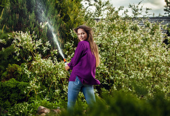 Beautiful joyful young girl in violet casual shirt poses in a summer garden with water hose.