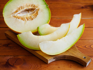 Slices of fresh and sweet melon on wooden board