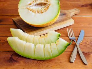 Honeydew  melon sliced on wooden background