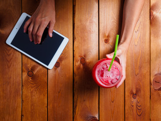Girl in the restaurant with a cocktail and a tablet