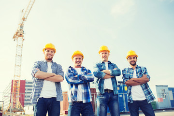 Fototapeta group of smiling builders in hardhats outdoors obraz