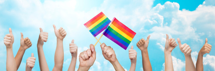 hands showing thumbs up and holding rainbow flags
