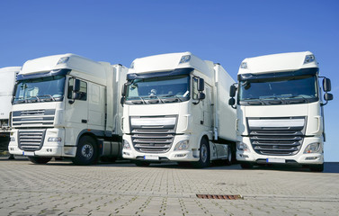 Spedition - Logistik, drei geparkte weiße Lastkraftwagen