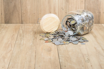 coins in glass bottle on wooden background