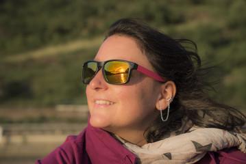 Glückliche Frau strahlt mit Sonnenuntergang um die Wette