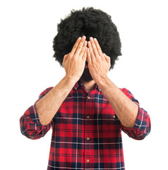 Afro man covering his eyes