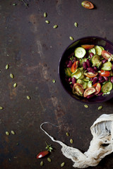 summer salad with fresh vegetables and seeds on bowl on a rusty surface with cloth