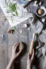Person handling a dough with a rolling pin over a wooden table with ingredients