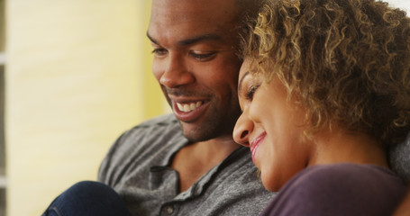 Black couple sitting on couch smiling