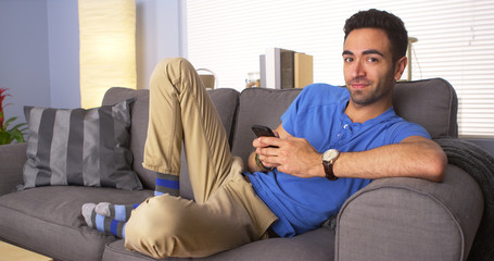 Attractive Mexican man lying on couch