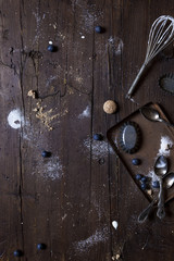 Aged wood surface with kitchen used tools and sprinkled with ingredients