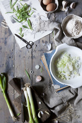 sliced and whole fresh spring onions on rustic table with ingredients