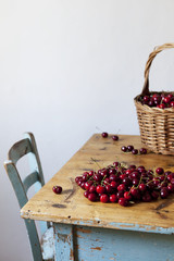 Freshly picked cherries in a basket and on rustic kitchen table