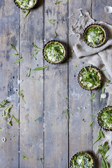 group of little quiche with green fresh vegetables and Parmesan cheese on wooden table