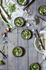 Preparation of little quiche with fresh ingredients on wooden rustic surface