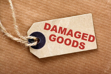 The description Damaged Goods on a luggage tag or price ticket on brown wrapping or parcel paper