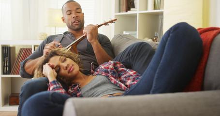 African boyfriend serenading his girlfriend with ukulele