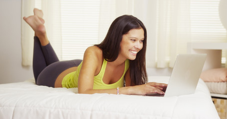 Happy mixed race woman using laptop on bed