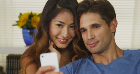 Happy interracial couple taking selfies
