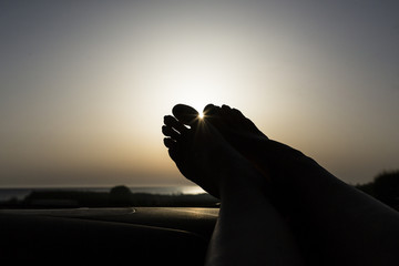 Feet on dashboard, driving on empty road on vacations, near the