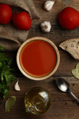 Tomato cream soup with ingredients on wooden background. Top vie