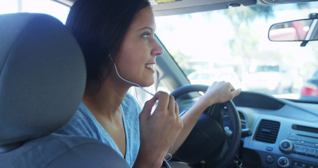 Mixed race woman talking in the car with earphones