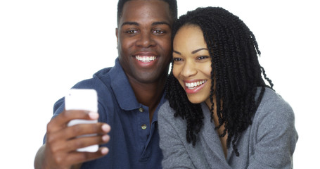 Happy young Black couple taking selfie together and laughing