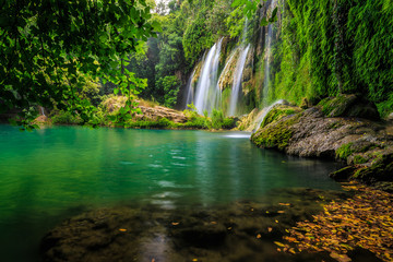 a beautiful waterfall in the forest on a river