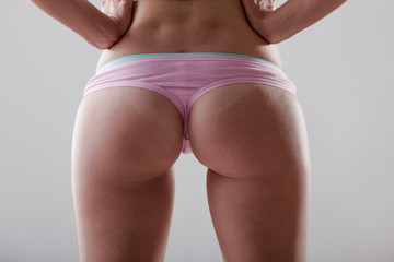Half body shot of sexy woman buttocks in pink underwear