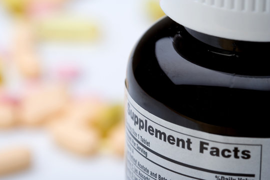 Vitamin Supplement Facts – A bottle of vitamins, with the supplement facts label showing. Vitamins in the background.