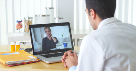 Mexican doctor video chatting with elderly patient