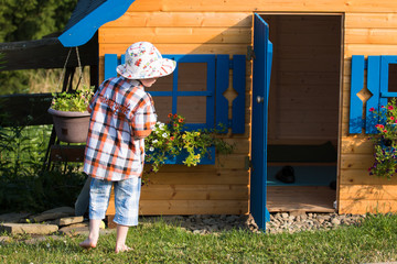 barefoot boy with hat playing at the playhouse in the summer garden