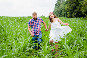 Happy loving young adult couple spending time on the field on sunny day outdoors. Handsome man and beautiful woman holding hands and running on field