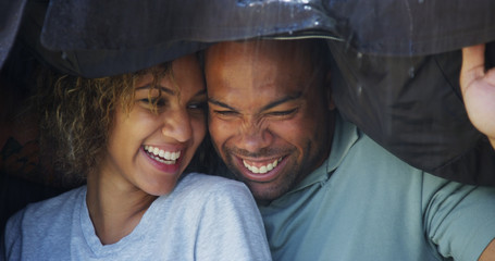 Black couple standing under coat trying not to get wet