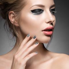 Beautiful girl with bright creative fashion makeup and Grey nail